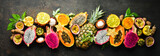 Tropical fruits on a brown background: papaya, mangosteen, cactus fruit, pytahaya, pineapple. Top view. Free space for text.