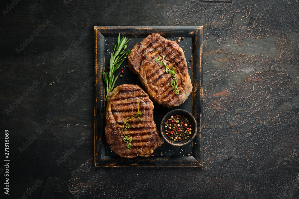 Fototapeta Grilled ribeye beef steak, herbs and spices on a dark table. Top view. Free space for your text.