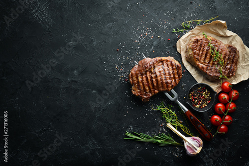 Recess Fitting Steakhouse Grilled ribeye beef steak on the fork. At the aged table. Top view. Free space for your text.