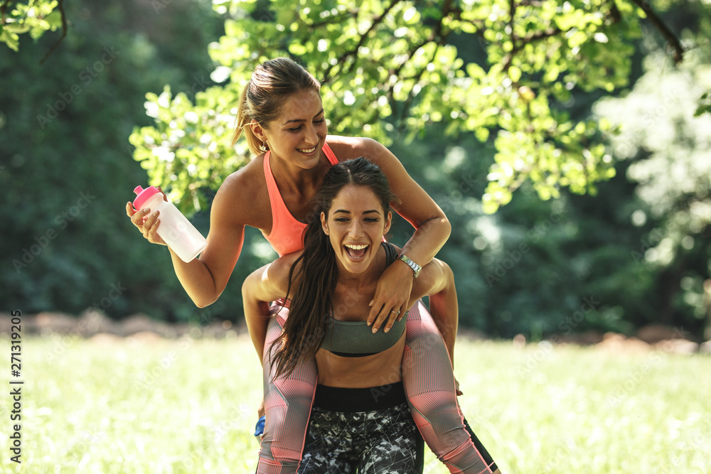 Fototapety, obrazy: Two best female friends making fun after jogging and workout.They laughing and carrying each other.Spring time.