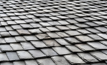 Aged Black Slate Roof Tiles Background. Perspective View.
