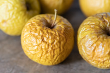 Wrinkled Yellow Old Apples Lies On The Table Top.