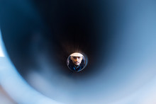 Man Looking Through A Pipe