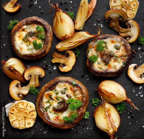 Fototapeta Stuffed portobello mushrooms stuffed with mozzarella and gorgonzola cheese and aromatic herbs on a black background, top view. Vegetarian food obraz