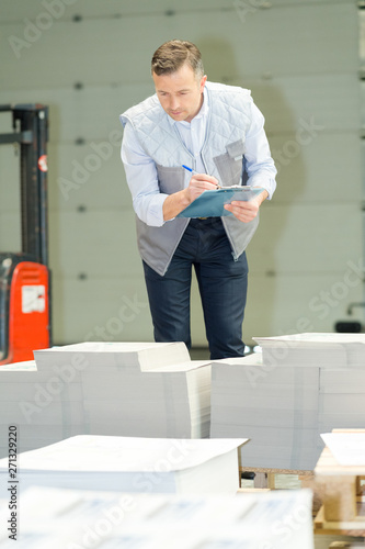 Valokuva  portrait of mid adult male counting paper in factory