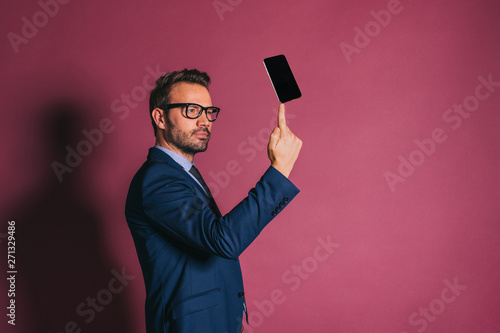 Fotografía  Businessman holding mobile phone with a finger
