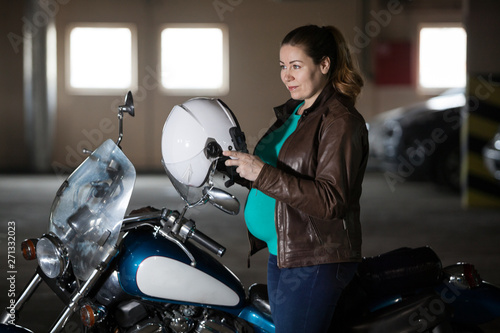Motorcyclist pregnant woman preparing to ride chopper bike, put on helmet at parking lot