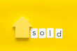Mortgage credit concept with house toy and sold copy on yellow background top view