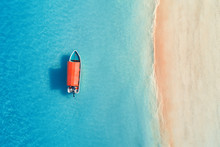 Aerial View Of The Fishing Boat In Clear Blue Water At Sunny Day In Summer. Top View From The Air Of Boat, Sandy Beach. Indian Ocean In Zanzibar, Africa. Landscape With Motorboat And Clear Sea. Travel