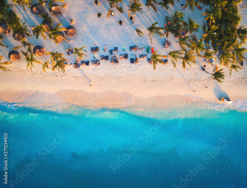 Printed kitchen splashbacks Zanzibar Aerial view of umbrellas, palms on the sandy beach of Indian Ocean at sunset. Summer travel in Zanzibar, Africa. Tropical landscape with palm trees, parasols, people, sand, blue water, waves. Top view