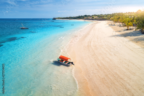 Aerial view of the fishing boat in clear blue water at sunset in summer. Top view of boat, sandy beach, palm trees. Indian ocean. Travel in Zanzibar, Africa. Colorful landscape with motorboat, sea
