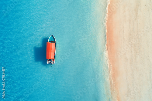 Fotobehang Blauw Aerial view of the fishing boat in clear blue water at sunny day in summer. Top view from the air of boat, sandy beach. Indian ocean in Zanzibar, Africa. Landscape with motorboat and clear sea. Travel