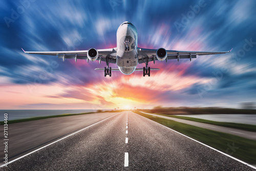 Türaufkleber Flugzeug Airplane and road with motion blur effect at sunset. Landscape with passenger airplane is flying over asphalt road and colorful sky. Commercial plane is landing. Aircraft with blurred background