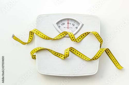 Fotografia Diet concept with scale and measuring tape for weight loss on white background t