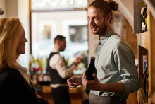 Waist Up Portrait Of Smiling Young Man Consulting Customer In Liquor Store, Copy Space