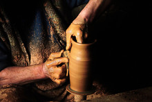 Close Up Mud Covered Hands Of Adult Man Making Clay Pot On Potter's Wheel