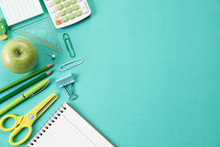 Education Or Back To School Concept. Top View Of Colorful School Supplies With Books, Color Pencils, Calculator, Pen Cutter Clips And Apple On Green Pastel Background. Flat Lay.