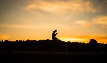 Concept Of Religion Islam. Silhouette Of Man Praying On The Background Of A Mosque At Sunset