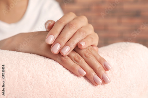 Poster Manicure Woman showing neat manicure on towel, closeup. Spa treatment