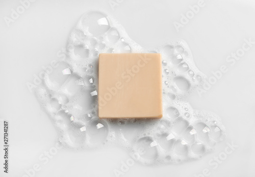Fototapeta Soap bar and foam on white background, top view