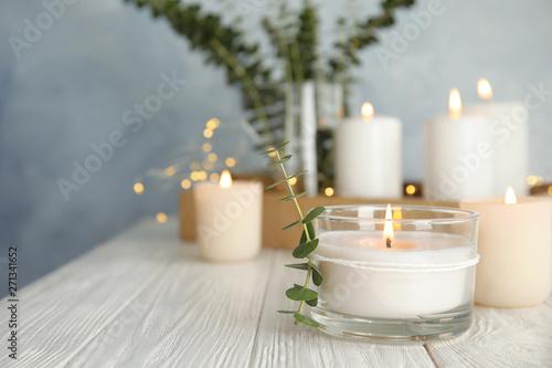 Obraz na płótnie Burning aromatic candle and eucalyptus branch on table