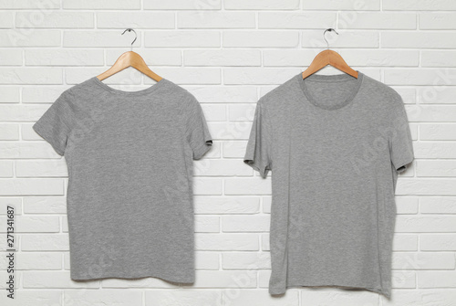 Hangers with blank t-shirts on white brick wall  Mock up for