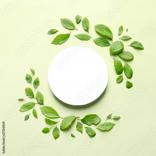 Flat lay composition with blank card and spring green leaves on color background. Space for text