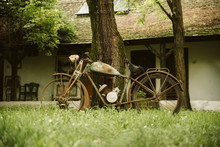 An Old Rusty Bicycle In Front Of The House