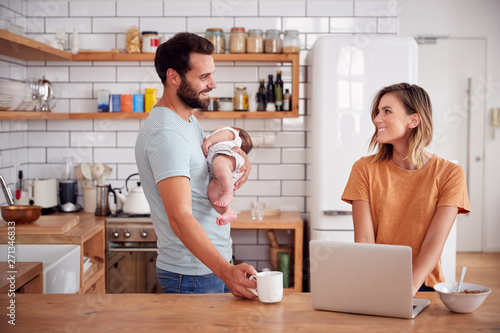 Multi-Tasking Father Holds Baby Son And Makes Hot Drink As Mother Uses Laptop And Eats Breakfast - 271346833