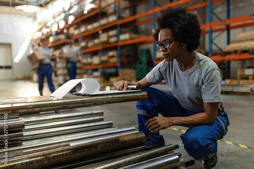 Photo  Black female worker checking list of products in a warehouse.