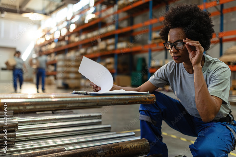 Fototapety, obrazy: African American woman going through paperwork while working in a warehouse.