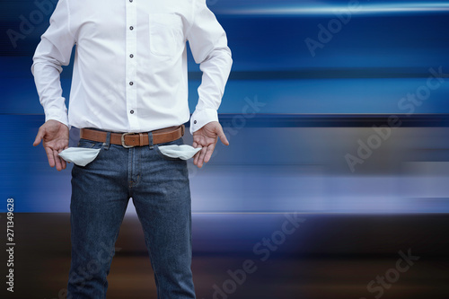 Fotografía Man showing his empty pockets on abstract modern blue background.