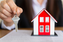 Your New House, Real Estate Agent Holding House Key To His Client After Signing Contract Agreement In Office,concept For Real Estate, Renting Property