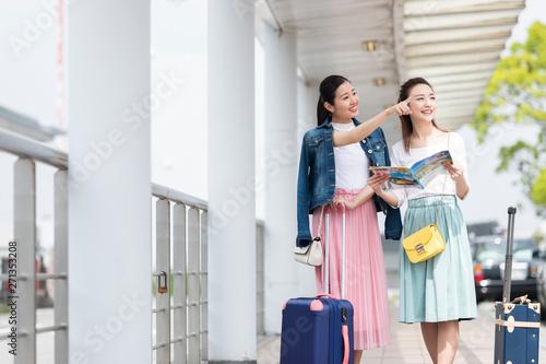 Fototapeta キャリーケースを引いて歩く女性2人 obraz