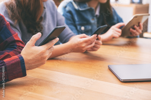 Three young asian people using and looking at mobile phone and tablet pc Canvas Print