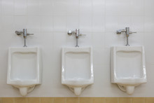 Row Of White Urinals In Men To...