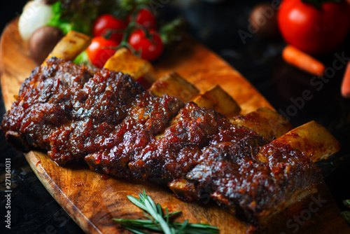 Fotografia BBQ beef ribs steak served with a hot chili pepper and fresh tomatoes on an old