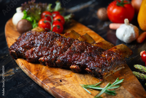 Obraz na plátně BBQ beef ribs steak served with a hot chili pepper and fresh tomatoes on an old