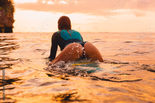 Foto op Canvas Ontspanning Attractive surf girl with perfect body on surfboard in ocean. Surfing at sunset time