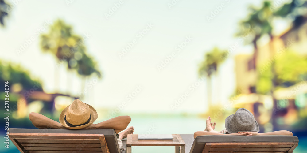 Fototapeta Summer resort hotel stay relaxation with tourist traveller couple take it easy happily resting on beach chair on holiday travel vacation poolside peacefully at tropical beach swimming pool