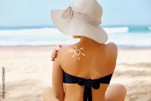Suncream. Suntan Lotion Beautiful Woman Applying on beautiful on Shoulder In Form Of The Sun. Sunscreen Solar Cream. Skin care. Sun protection.The Girl Uses  Moisturizer Sunblock