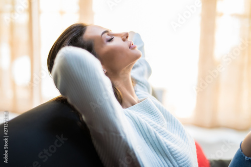 Fototapety, obrazy: Portrait of a girl relaxing on a sofa after work at home sitting on a sofa in the living room at home with a warm light of sunset