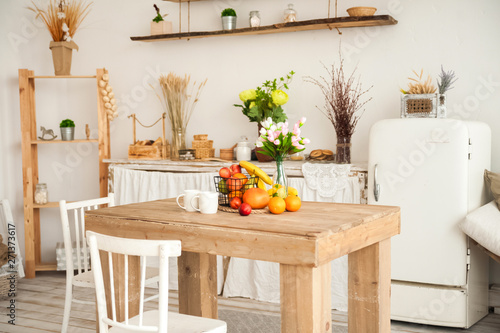Concept breakfast made from fruits and coffee or tea. Oranges, bananas, cups, peaches on a textural large wooden table against a background of rustic or Scandinavian cuisine