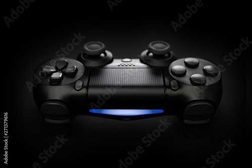 Closeup photo of video game console gamepad joystick controller on black background with blue light.