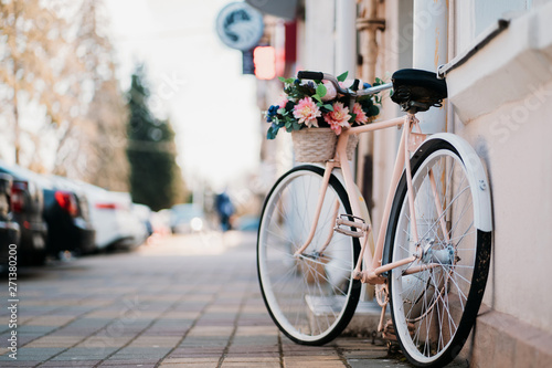 Papiers peints Velo White bicycle with basket of flowers standing near the door on the street in city.