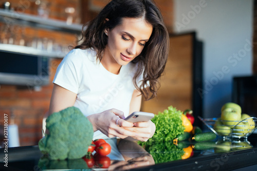Fotografia  Smiling young woman text messaging in front of vegetables in the kitchen at home