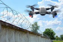 Security Drone Patrols The Territory Across The Sky. Guarding The Wall With Barbed Wire Drone With Blue And Red Beacon
