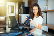 Young freelance woman photographer at home, working on laptop in home office
