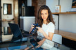 Freelance photographer woman with camera at home office editing photos on laptop