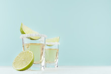 Alcohol Cocktail - Tequila With Salty Rim, Piece Lime In Shot Glasses In Modern Elegant Pastel Blue Interior, Copy Space.